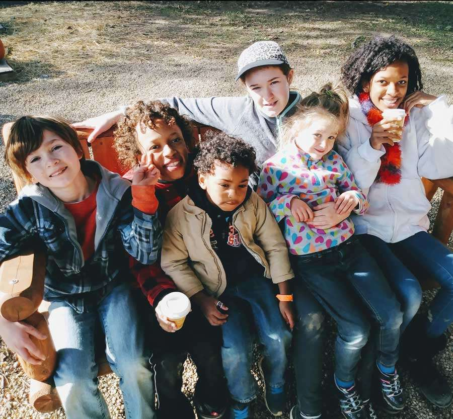 a group of young kids smiling sitting together